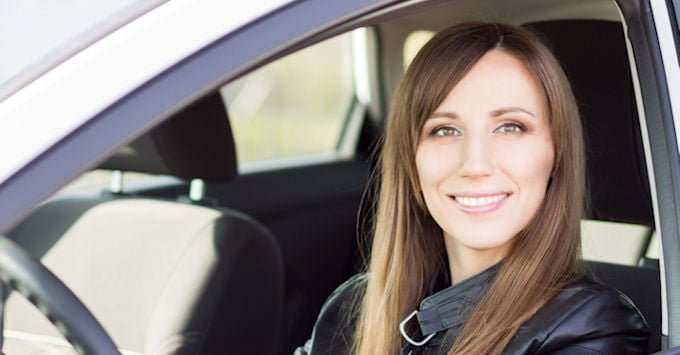Young woman behind the wheel of her car